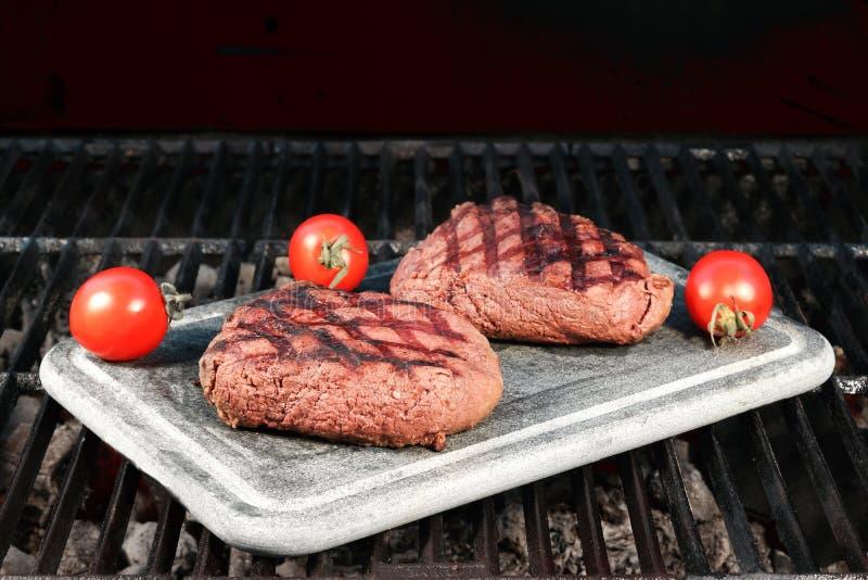 Twee Geroosterde Rundvleeslapjes vlees met Tomaten aan boord bij de Grill royalty-vrije stock afbeelding