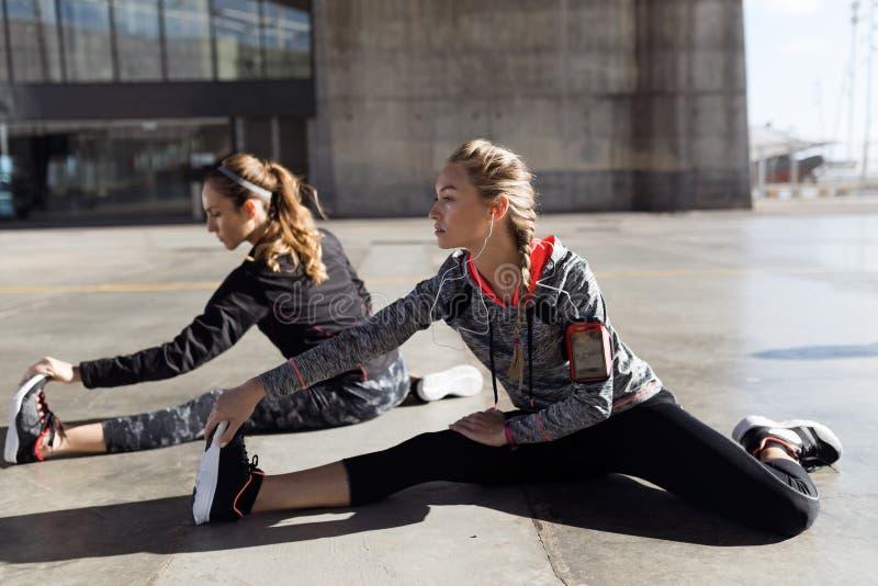 Twee geschikte en sportieve jonge vrouwen die het uitrekken in stad doen zich stock foto
