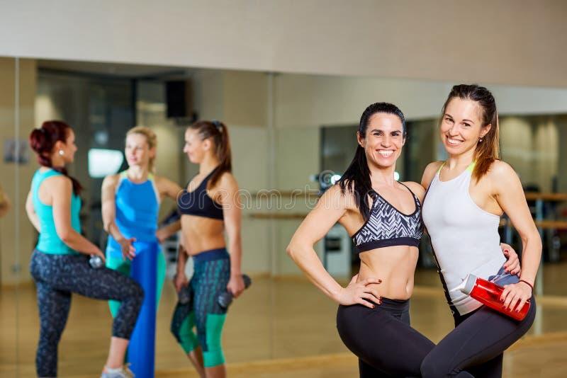 Twee geschiktheidsmeisjes in de gymnastiek van groep opleiding royalty-vrije stock afbeelding