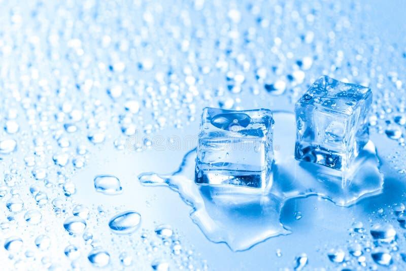 Twee gesmolten ijsblokjes met waterdalingen stock afbeeldingen