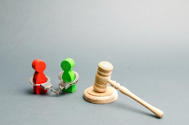 Twee gevangenen in handcuffs en de hamer van een rechter Overtreders van de wet Overweging van het geval Het oordeel en het hof royalty-vrije stock foto