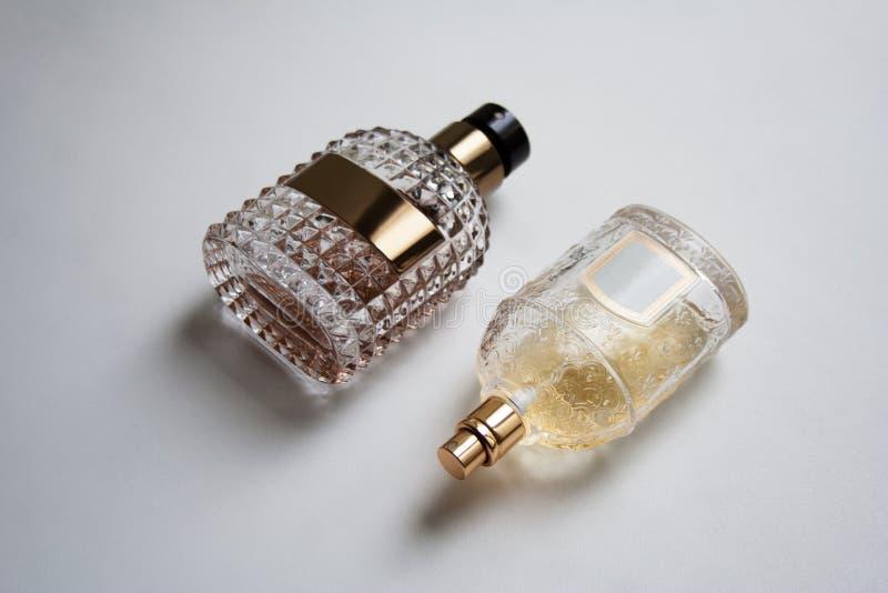 Twee geweven flessen van het glasparfum met glanzende gouden details stock afbeeldingen