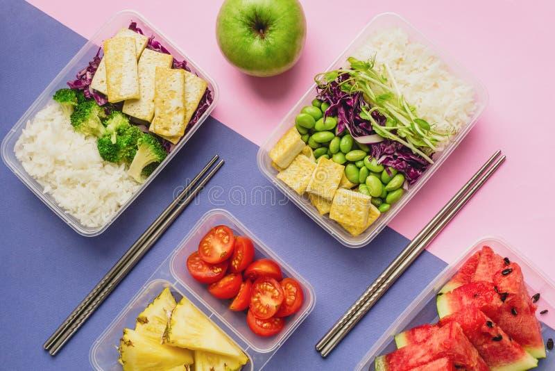 Twee gezonde Aziatisch-stijl op installatie-gebaseerde lunchdozen knolled samen op blauwe en roze achtergrond stock fotografie