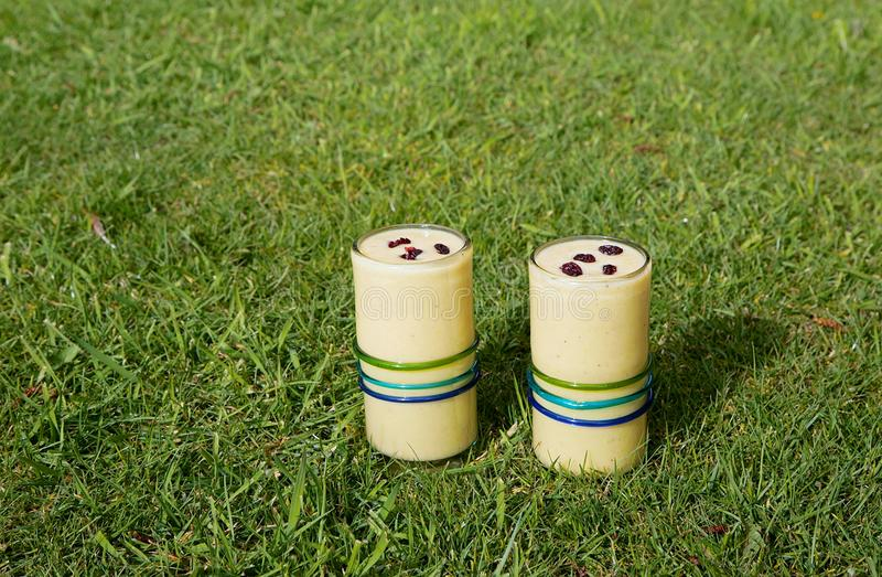 Twee gezonde dranken, gele smoothies met rode Amerikaanse veenbessen op bovenkant stock afbeeldingen