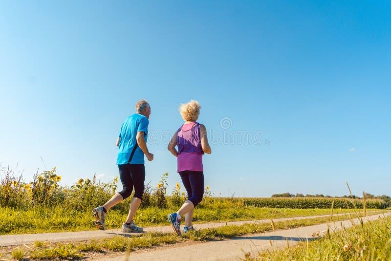 Twee gezonde hogere mensen die op een landweg in de zomer aanstoten royalty-vrije stock foto's