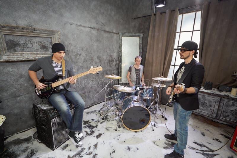 Twee gitaristen en slagwerkerspel in ruimte stock afbeelding