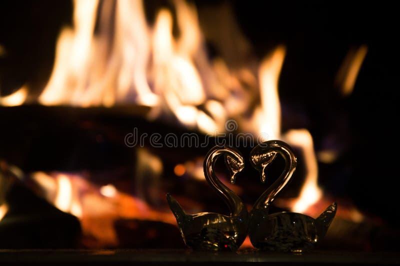 Twee glaszwanen in de vorm van een hart dichtbij de open haard stock afbeelding