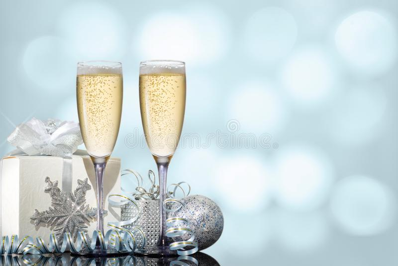 Twee glazen champagne met een gift en Kerstmisspeelgoed op een turkooise achtergrond stock foto's
