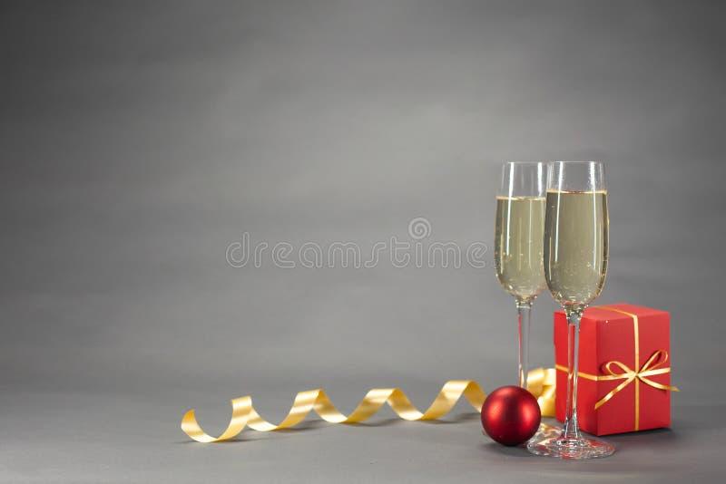 Twee glazen champagne naast Kerstmis huidig in rood royalty-vrije stock foto