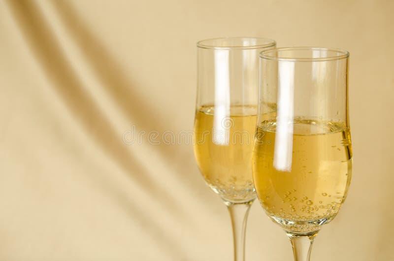 Twee glazen champagne op een achtergrond van een stof van gouden c royalty-vrije stock afbeelding