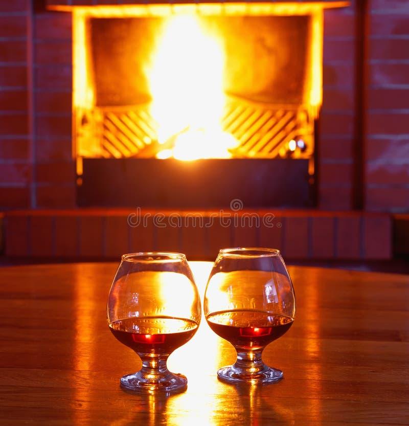 Twee glazen cognac op de oude baksteenopen haard met heldere brand royalty-vrije stock fotografie