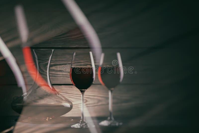 Twee glazen en karaf rode wijn op een donkere achtergrond stock foto