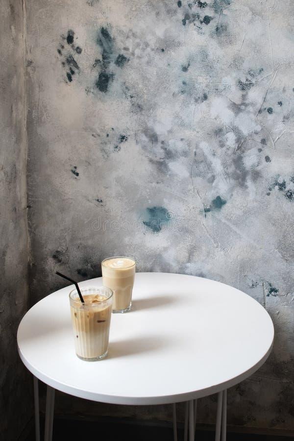 Twee glazen koffie op witte lijst in koffie stock foto