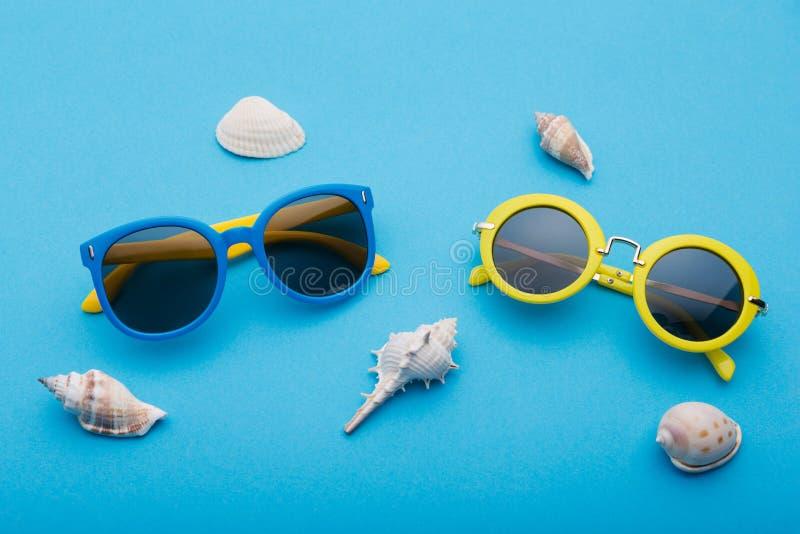 Twee glazen liggen op een blauwe achtergrond, blauwe en gele die glazen door overzeese shells, de conceptenzomer en reis wordt om royalty-vrije stock afbeeldingen