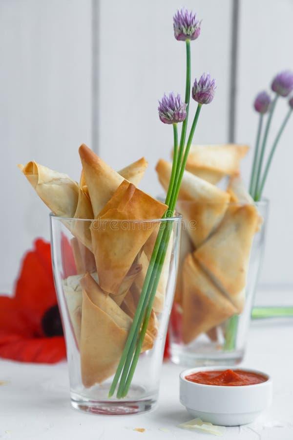 Twee glazen met de pastei van phyllodriehoeken met feta en spinazie royalty-vrije stock fotografie