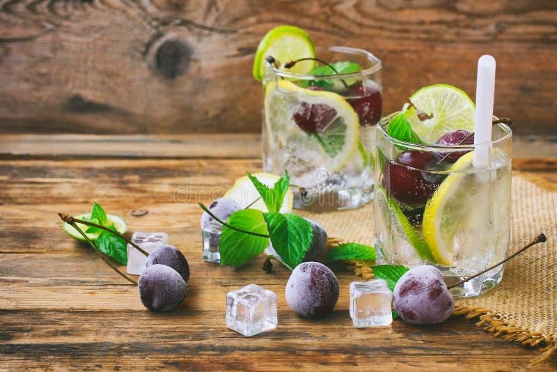 Twee glazen met drank met stro, bevroren kersen, citroen, kalk stock foto