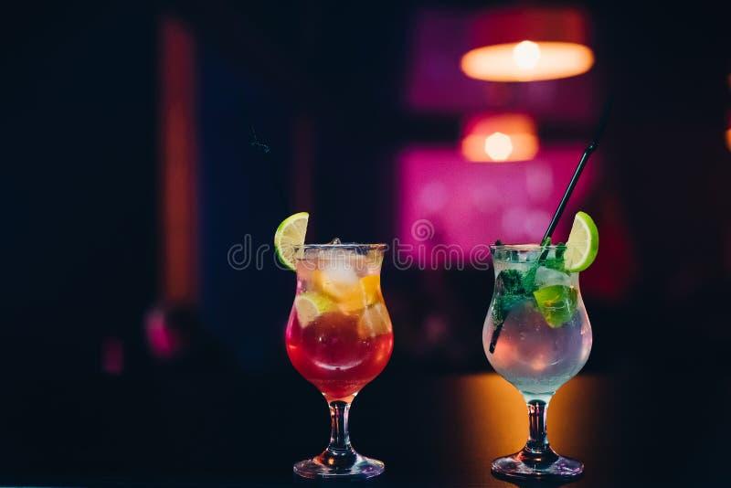 Twee glazen met fruitcocktails met kalk, sinaasappel en munt en stro bij partij op bar royalty-vrije stock afbeelding