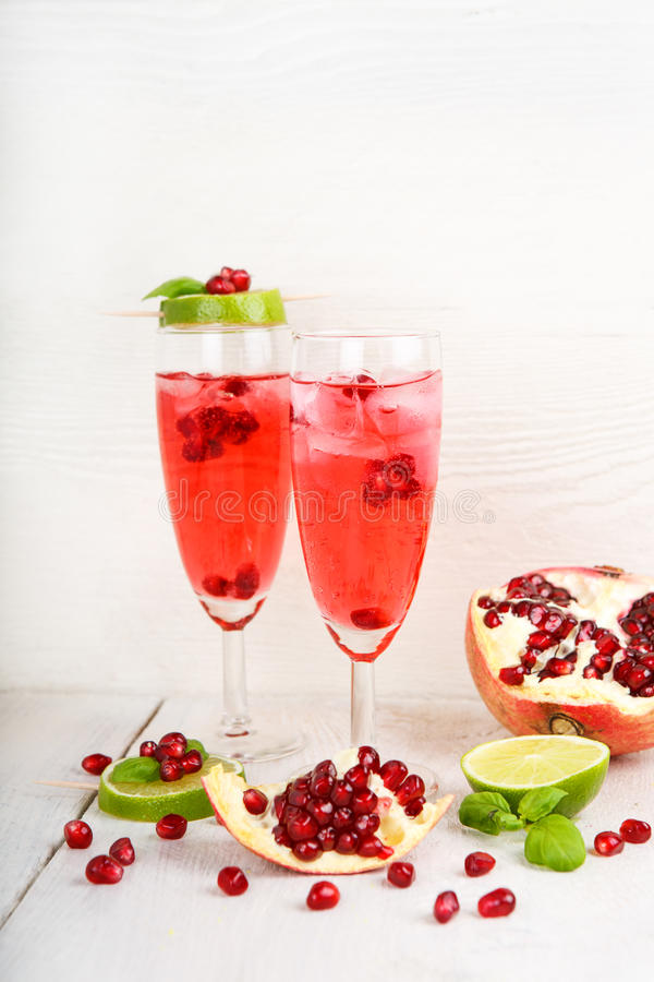 Twee glazen met rode pomgranatechampagne, kalk en munt. royalty-vrije stock foto