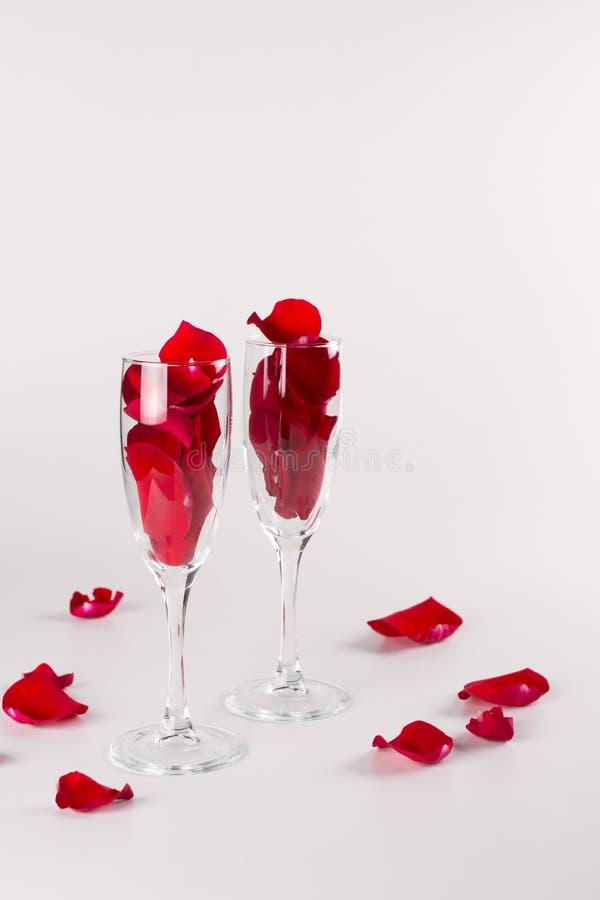 Twee glazen met roze bloemblaadjes op witte achtergrond Het concept van de viering De ruimte van het exemplaar stock foto's
