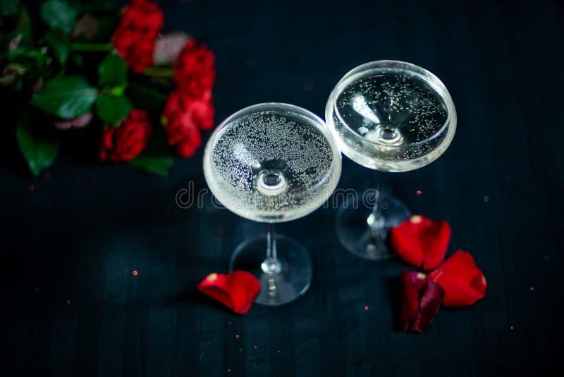 Twee glazen met witte champagne en bloemblaadjes van rode rozen op de zwarte achtergrond stock afbeeldingen