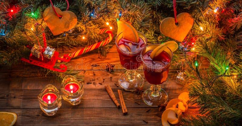 Twee glazen overwogen wijn met oranje plakken, kaarsen en Kerstboom met slinger en speelgoed royalty-vrije stock afbeeldingen