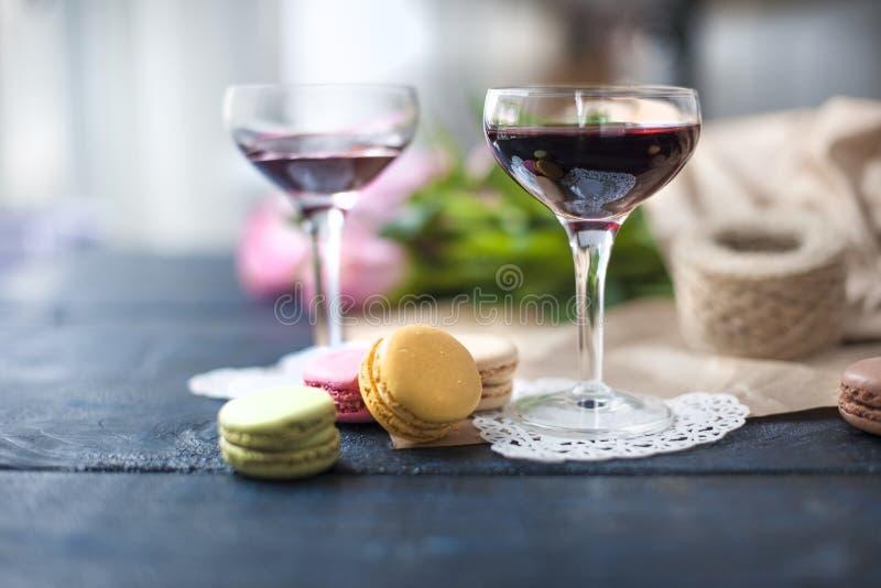Twee glazen rode wijn Een boeket van roze rozen in pakpapier De macaroni van het kleurengebakje Dichtbij het venster Vrije ruimte royalty-vrije stock fotografie
