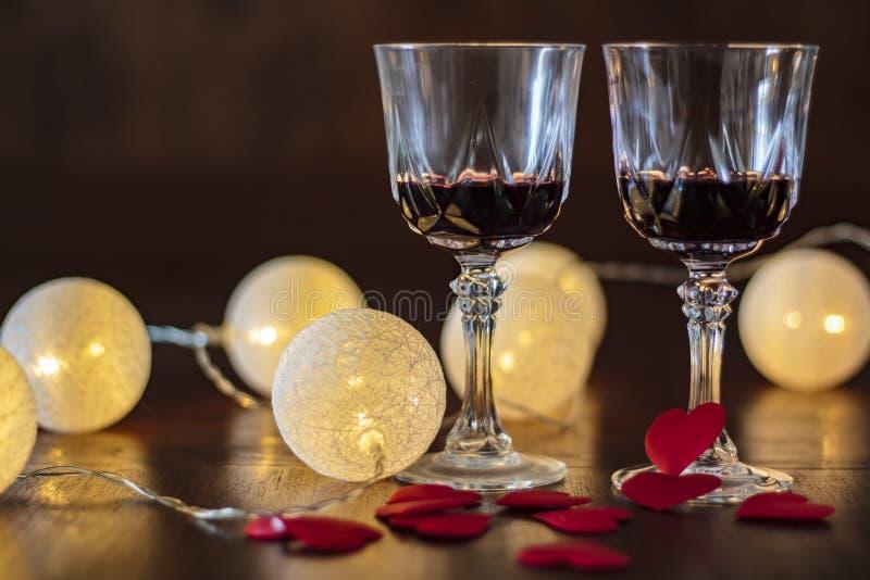 Twee glazen rode wijn en harten op een houten lijst stock fotografie