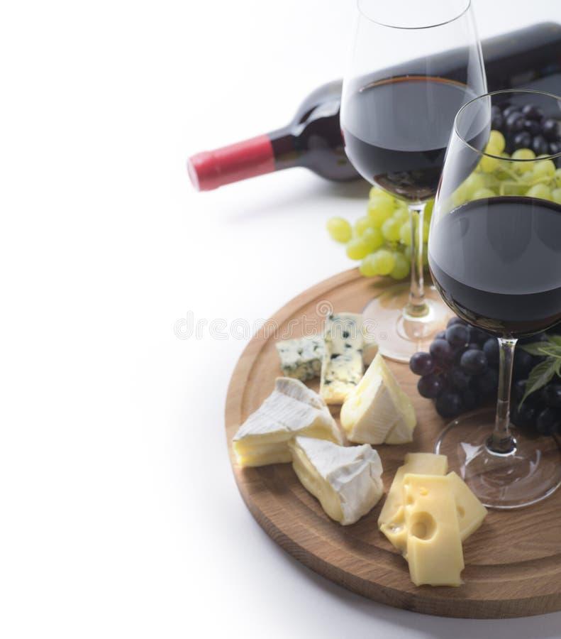 Twee glazen rode wijn, fles, kaas en druiven stock foto's