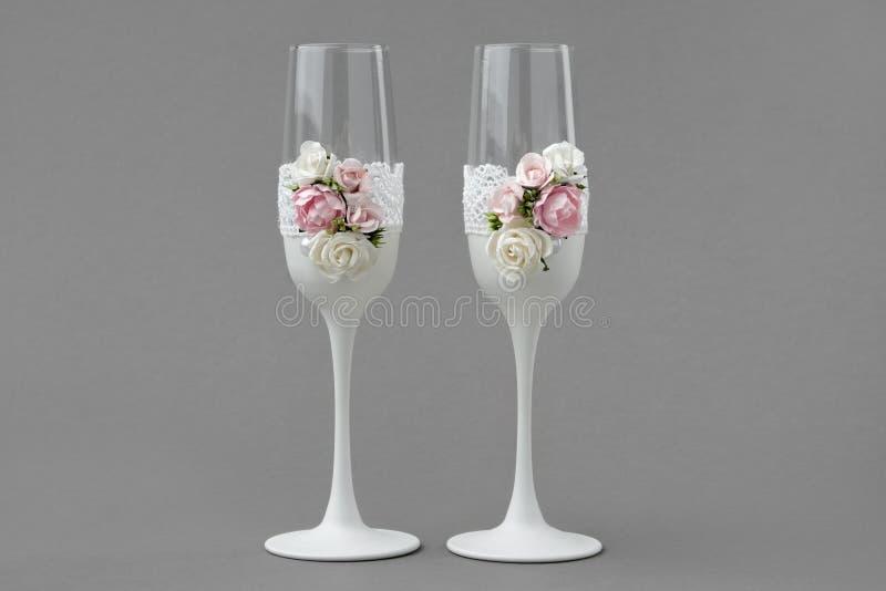 Twee glazen van de huwelijkswijn die met kant en rozen op grijze achtergrond worden verfraaid royalty-vrije stock afbeelding