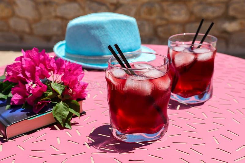 Twee glazen van de zomer rode cocktail met ijs naast een boek, een twijg van Bougainvillea bloeit, blauwe hoed op een roze lijst stock foto