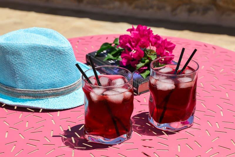 Twee glazen van de zomer rode cocktail met ijs naast een boek, een twijg van Bougainvillea bloeit, blauwe hoed op een roze lijst royalty-vrije stock foto's