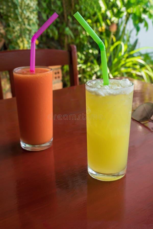 Twee glazen van fruit smoothie, ananas en tomaat op een rode lijst bij koffie stock fotografie
