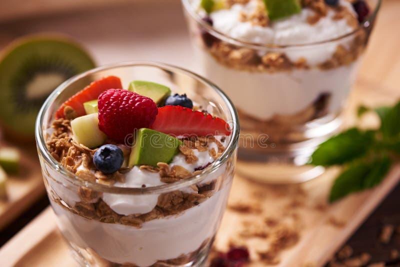 Twee glazen van heerlijke yoghurt en vruchten ionen houten lijst royalty-vrije stock afbeelding