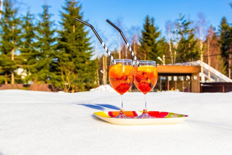 Twee glazen van koude Aperol Spritz op dienblad van sneeuw op zonnige ijzige dag in de winter, pijnbomen en sparren op achtergron stock foto's