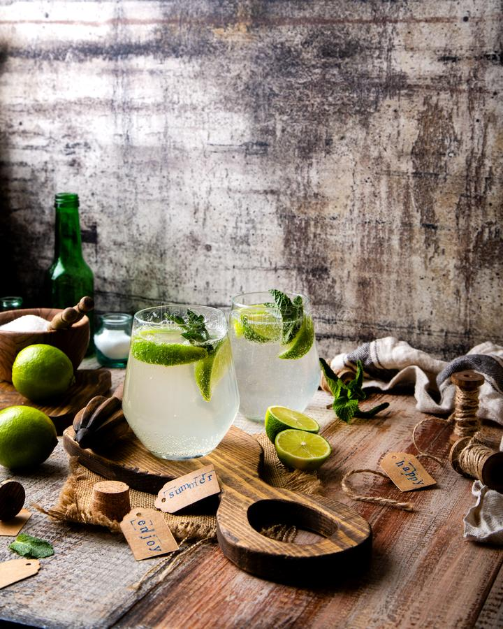 Twee glazen van koude ijzige mojito van de de zomercocktail met muntbladeren en plakken van kalk stock foto