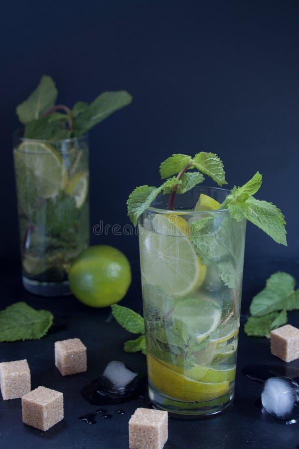 Twee glazen van mojitococktail met verse kalk en munt De ijsblokjes en de stukken van bruine suiker liggen op een lijst stock fotografie