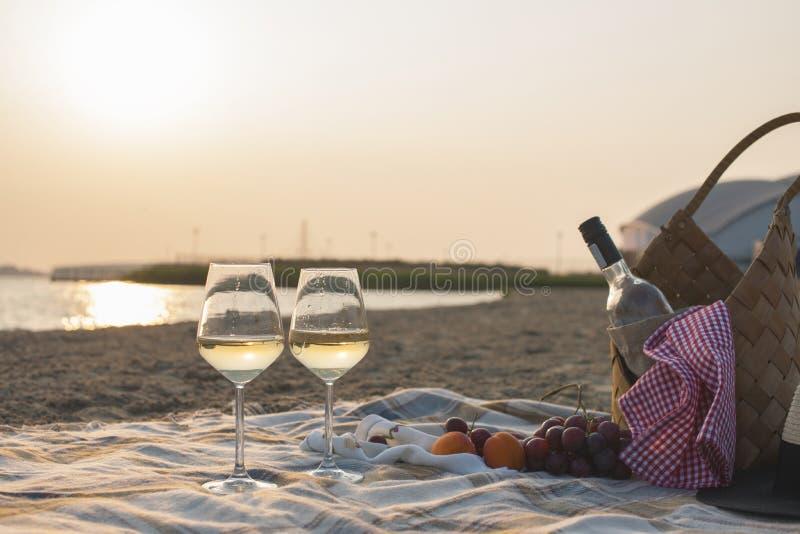 Twee glazen van wijn en een mand voor een picknick Romantisch op het strand en de zonsondergang Vakantie Vrije ruimte voor tekst  stock fotografie