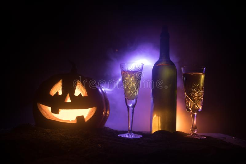 Twee glazen van wijn en fles met Halloween - oude hefboom-o-lantaarn op donkere gestemde mistige achtergrond Enge Halloween pompo royalty-vrije illustratie