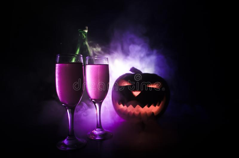 Twee glazen van wijn en fles met Halloween - oude hefboom-o-lantaarn op donkere gestemde mistige achtergrond Enge Halloween pompo stock fotografie