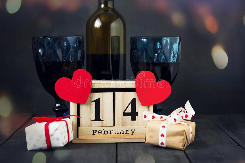 Twee glazen van wijn met een document hart en een kalender met een datum op 14 Februari, en een gift Op houten dark royalty-vrije stock foto's