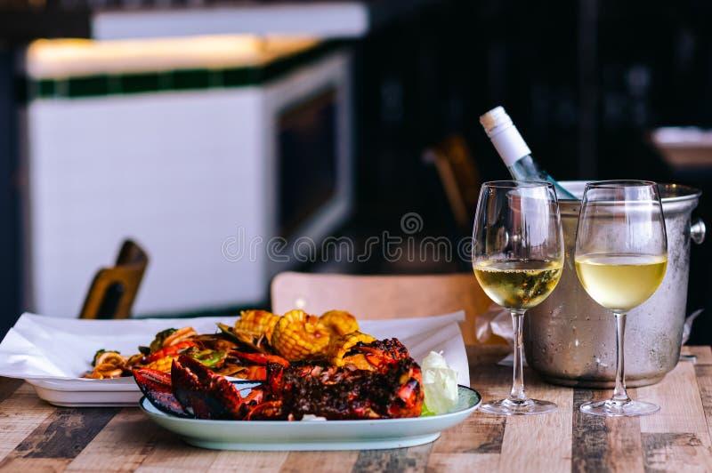 Twee glazen van witte wijn op de lijst met een fles in wijn koelere emmer en zeevruchtenschotel voor paar het dineren stock foto