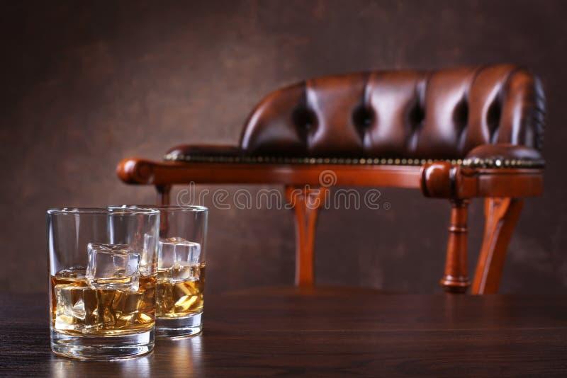 Twee glazen whisky met ijsblokjes op lijst royalty-vrije stock afbeelding