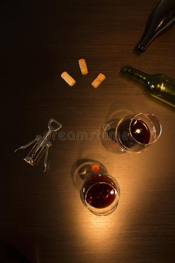 Twee glazen wijn met een lege fles, een kurketrekker en wat kurkt in donkere tonen royalty-vrije stock fotografie