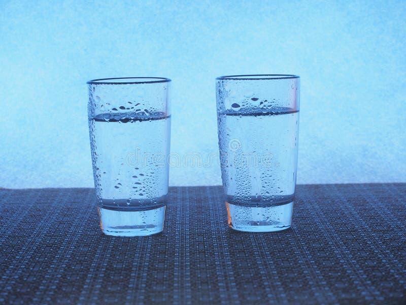 Twee glazen wodka zijn op de lijst De glazen zijn behandeld met waterdruppeltjes royalty-vrije stock foto