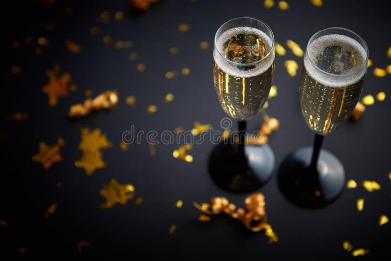 Twee glazenhoogtepunt van fonkelende champagnewijn met gouden decoratie stock foto