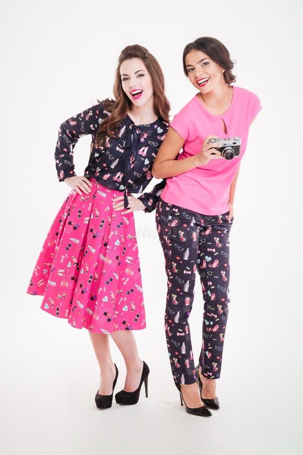Twee glimlachende aantrekkelijke jonge vrouwen met oude uitstekende camera stock foto's