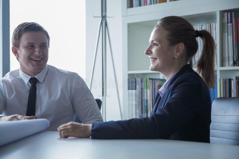 Twee glimlachende architecten die over een blauwdruk in het bureau bespreken, royalty-vrije stock afbeeldingen