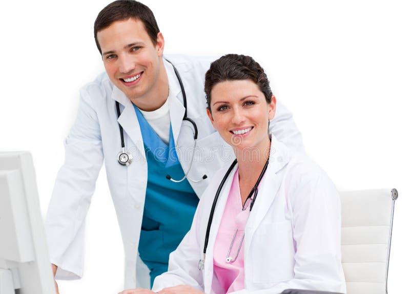 Twee glimlachende artsen die bij een computer werken royalty-vrije stock afbeeldingen