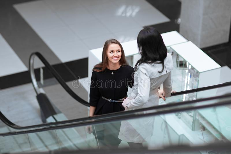 Twee glimlachende bedrijfsvrouwen die zich op een roltrap in een commercieel centrum bevinden royalty-vrije stock afbeelding