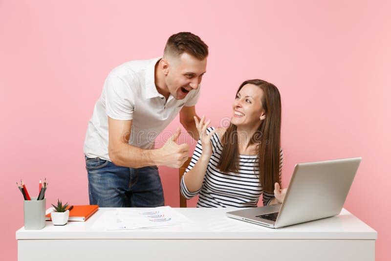 Twee glimlachende bedrijfsvrouwenman collega's zitten het werk bij wit bureau met eigentijdse laptop op pastelkleur roze achtergr royalty-vrije stock fotografie
